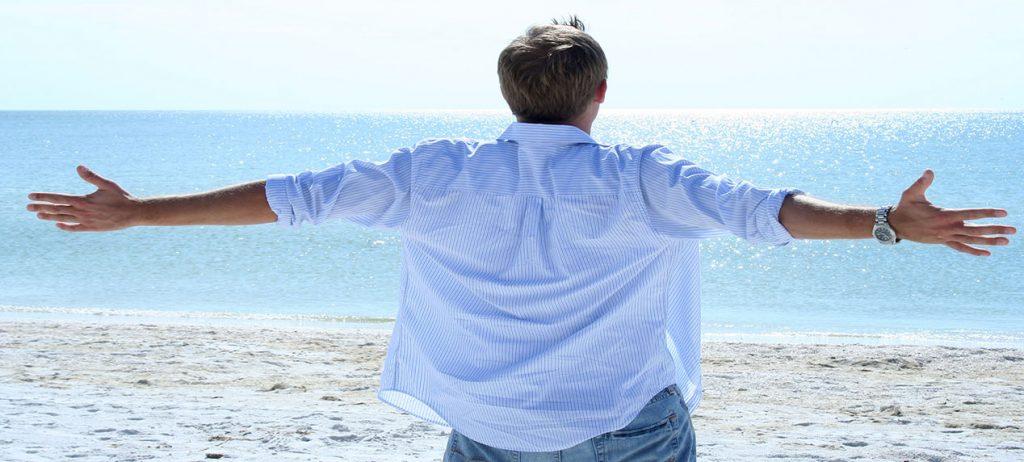 Un homme respirant bras ouverts, face à la mer -